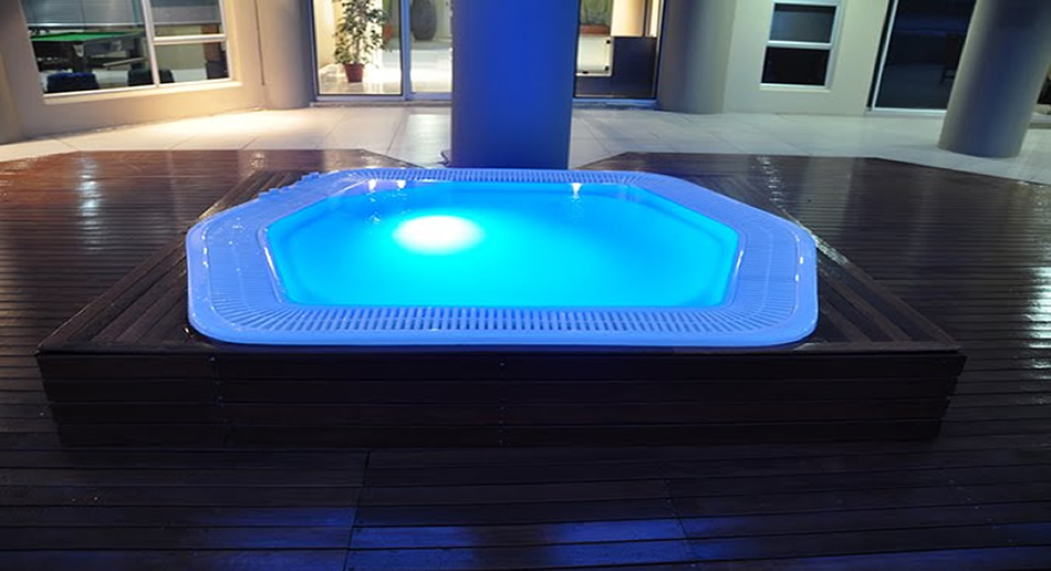 Rimflow Jacuzzi installed in wooden deck with blue LED light.